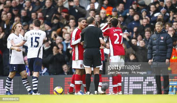 Arsenal's Emmanuel Eboue reacts after being shown red card by ferefee Mike Dean as Arsenal's manager Arsenen Wenger looks on Tottenham Hotspur's Luka...