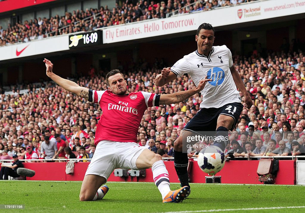 Arsenal's English defender Carl Jenkinson (L) vies with Tottenham Hotspur's Belgian midfielder Nacer Chadli (R) during the English Premier League football match between Arsenal and Tottenham Hotspur at the Emirates Stadium in north London on September 1, 2013. USE. No use with unauthorized audio, video, data, fixture lists, club/league logos or 'live' services. Online in-match use limited to 45 images, no video emulation. No use in betting, games or single club/league/player publications.