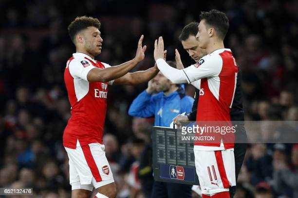 Arsenal's English midfielder Alex OxladeChamberlain is substituted for Arsenal's German midfielder Mesut Ozil during the English FA cup quarter final...