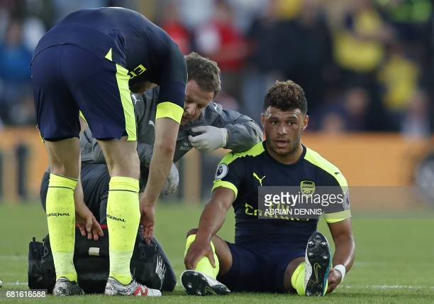 Arsenal's English midfielder Alex OxladeChamberlain receives medical attention after picking up an injury during the English Premier League football...