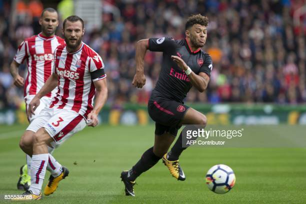 Arsenal's English midfielder Alex OxladeChamberlain runs away from Stoke City's Dutch defender Erik Pieters during the English Premier League...