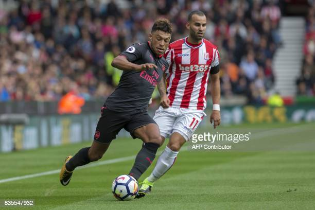 Arsenal's English midfielder Alex OxladeChamberlain runs away from Stoke City's Spanish striker Jese during the English Premier League football match...