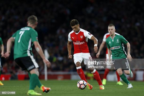 Arsenal's English midfielder Alex OxladeChamberlain runs with the ball during the English FA cup quarter final football match between Arsenal and...