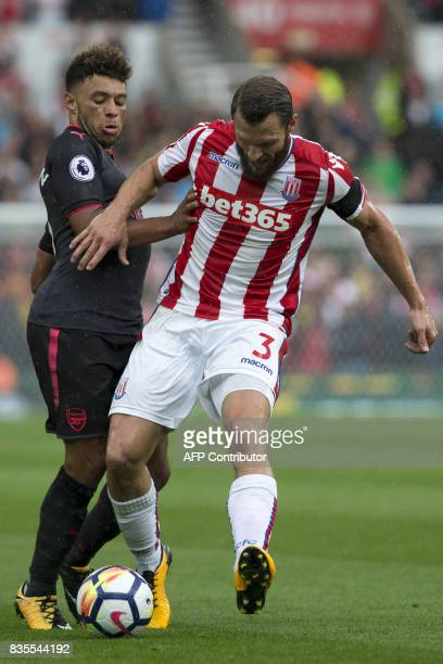 Arsenal's English midfielder Alex OxladeChamberlain vies with Stoke City's Dutch defender Erik Pieters during the English Premier League football...