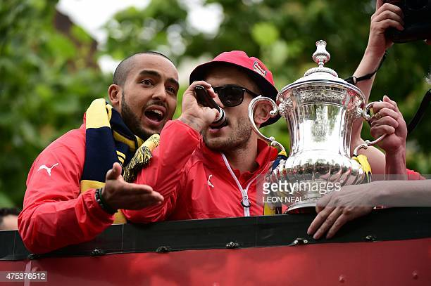 Arsenal's English midfielder Jack Wilshere and Arsenal's English midfielder Theo Walcott hold the trophy as they stand on the top deck of an...