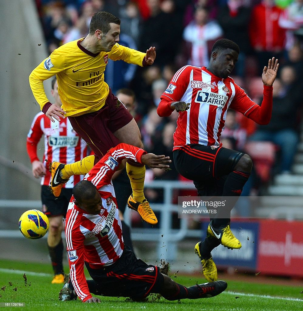 """Arsenal's English midfielder Jack Wilshere (up L) is tackled by Sunderland's French midfielder Alfred N'Diaye (R) and Sunderland's English defender Titus Bramble during the English Premier League football match between Sunderland and Arsenal at The Stadium Of Light, in Sunderland, north-east England, on February 9, 2013. USE. No use with unauthorized audio, video, data, fixture lists, club/league logos or """"live"""" services. Online in-match use limited to 45 images, no video emulation. No use in betting, games or single club/league/player publications."""