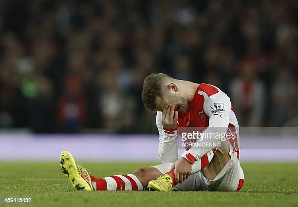 Arsenal's English midfielder Jack Wilshere lies injured during the English Premier League football match between Arsenal and Manchester United at the...