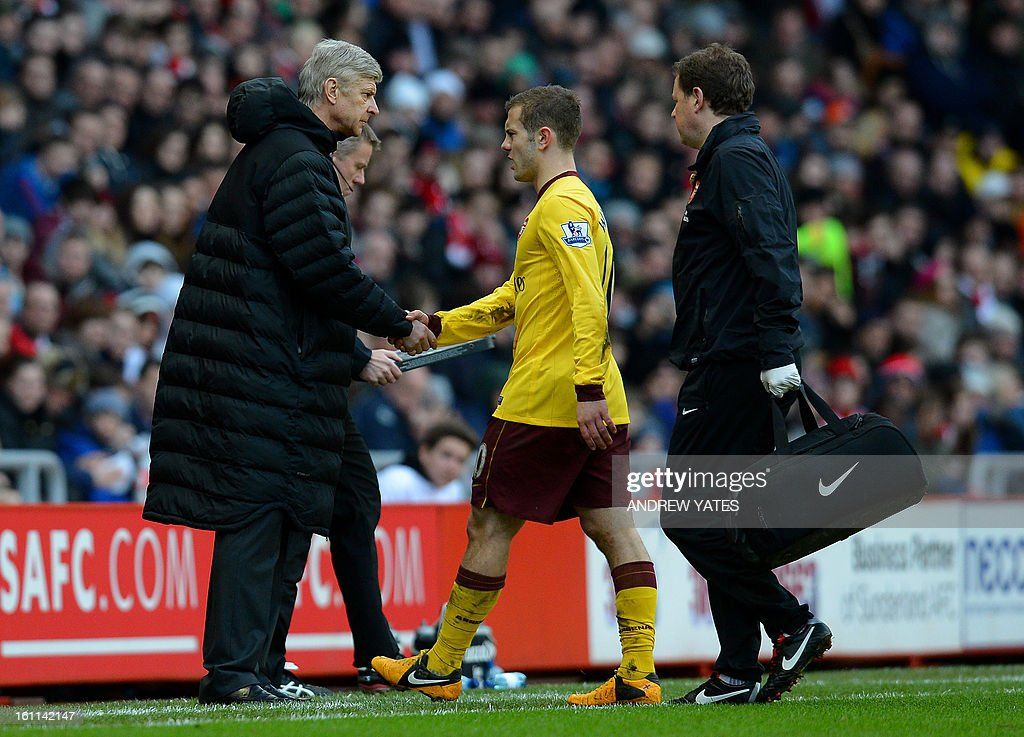 """Arsenal's English midfielder Jack Wilshere (C) shakes hands with Arsenal's French manager Arsene Wenger (L) after leaving the field injured during the English Premier League football match between Sunderland and Arsenal at The Stadium Of Light, in Sunderland, north-east England, on February 9, 2013. USE. No use with unauthorized audio, video, data, fixture lists, club/league logos or """"live"""" services. Online in-match use limited to 45 images, no video emulation. No use in betting, games or single club/league/player publications."""