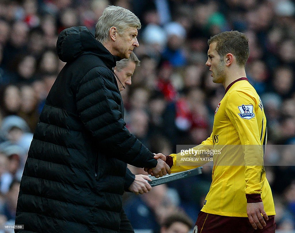 "Arsenal's English midfielder Jack Wilshere (R) shakes hands with Arsenal's French manager Arsene Wenger (L) after leaving the field injured during the English Premier League football match between Sunderland and Arsenal at The Stadium Of Light, in Sunderland, north-east England, on February 9, 2013. USE. No use with unauthorized audio, video, data, fixture lists, club/league logos or ""live"" services. Online in-match use limited to 45 images, no video emulation. No use in betting, games or single club/league/player publications."