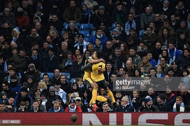 TOPSHOT Arsenal's English midfielder Theo Walcott celebrates scoring his team's first goal with Arsenal's Chilean striker Alexis Sanchez during the...