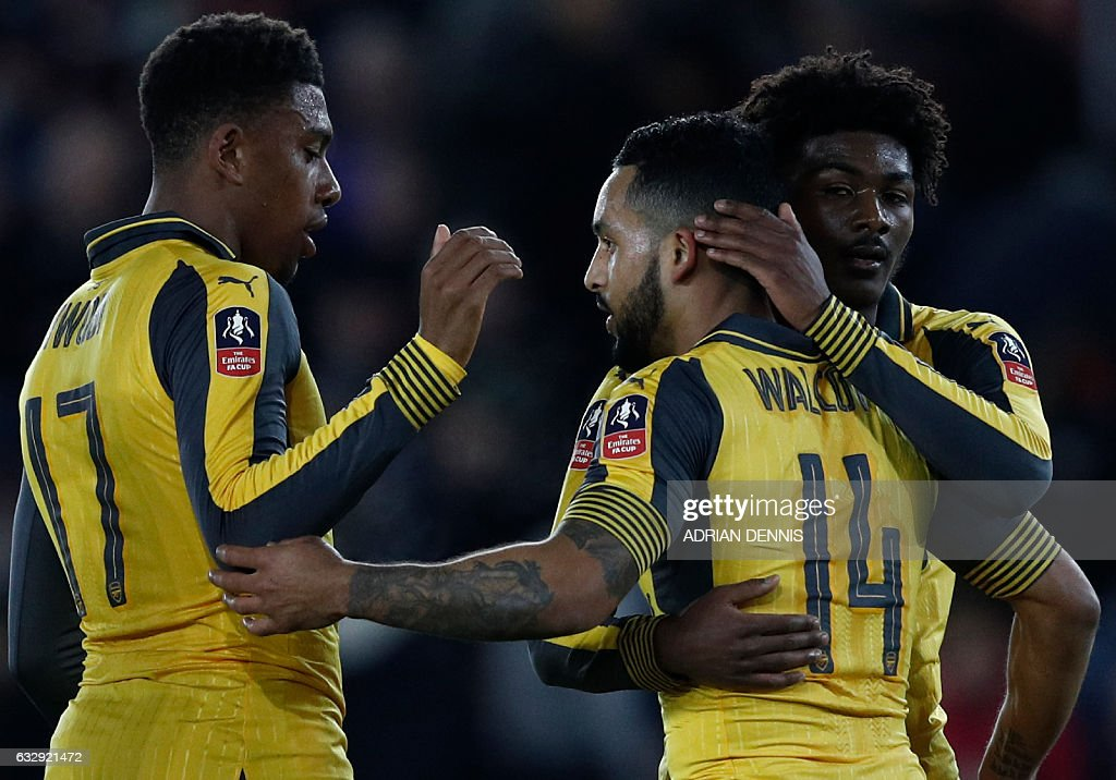 Arsenal's English midfielder Theo Walcott (C) celebrates scoring his team's fifth goal with Arsenal's Nigerian striker Alex Iwobi (L) and Arsenal's English midfielder Ainsley Maitland-Niles during the English FA Cup fourth round football match between Southampton and Arsenal at St Mary's in Southampton, southern England on January 28, 2017. / AFP / Adrian DENNIS / RESTRICTED TO EDITORIAL USE. No use with unauthorized audio, video, data, fixture lists, club/league logos or 'live' services. Online in-match use limited to 75 images, no video emulation. No use in betting, games or single club/league/player publications. /