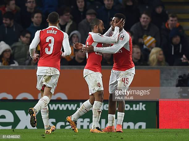 Arsenal's English midfielder Theo Walcott celebrates with Arsenal's Nigerian striker Alex Iwobi after scoring their third goal during the FA cup...