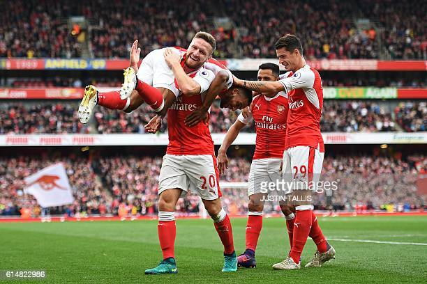 Arsenal's English midfielder Theo Walcott celebrates with Arsenal's German defender Shkodran Mustafi Arsenal's Chilean striker Alexis Sanchez and...