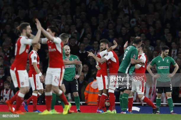 Arsenal's English midfielder Theo Walcott celebrates with Arsenal's French striker Olivier Giroud as Arsenal players celebrate Walcott's opening goal...