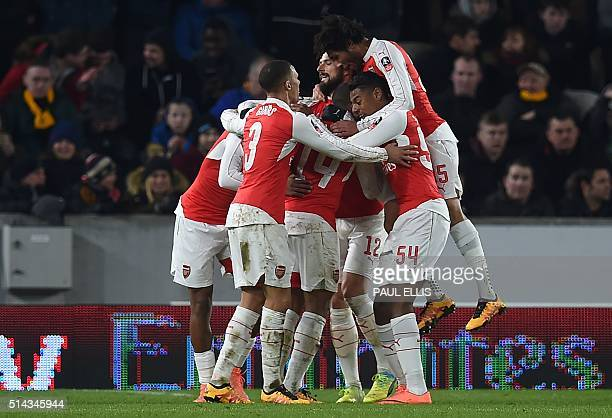 Arsenal's English midfielder Theo Walcott celebrates with teammates after scoring their third goal during the FA cup fifth round replay football...