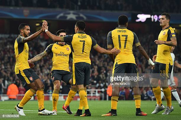 Arsenal's English midfielder Theo Walcott celebrates with teammates after scoring the opening goal of the UEFA Champions League Group A football...