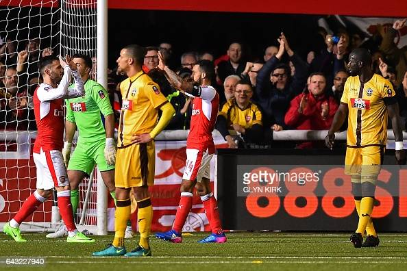Arsenal's English midfielder Theo Walcott celebrates with teammates after scoring their second goal his 100th goal for Arsenal during the English FA...
