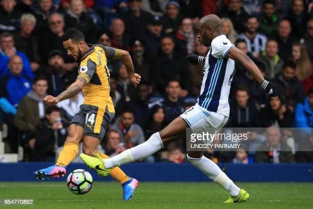 Arsenal's English midfielder Theo Walcott has a shot blocked by West Bromwich Albion's Frenchborn Cameroonian defender Allan Nyom during the English...