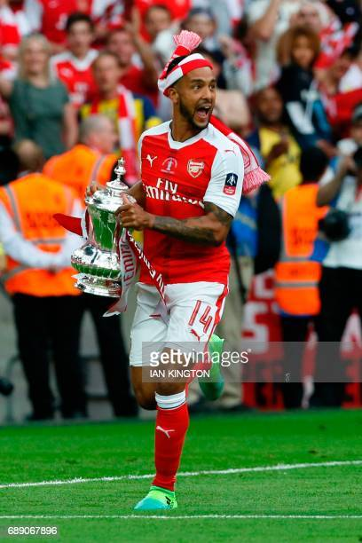 Arsenal's English midfielder Theo Walcott holds the FA Cup trophy as Arsenal players celebrate their victory over Chelsea on the pitch after the...