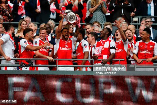 Arsenal's English midfielder Theo Walcott lifts the FA Cup trophy as Arsenal players celebrate their victory over Chelsea in the English FA Cup final...
