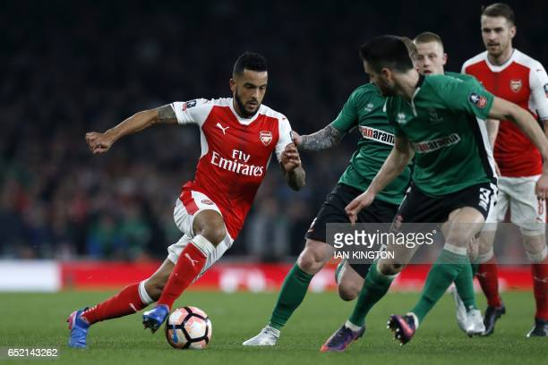Arsenal's English midfielder Theo Walcott runs with the ball during the English FA cup quarter final football match between Arsenal and Lincoln City...