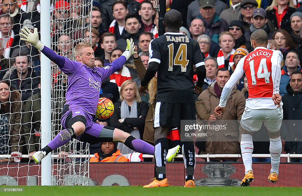 Arsenal's English midfielder Theo Walcott (R) scores his team's first goal past Leicester City's Danish goalkeeper Kasper Schmeichel during the English Premier League football match between Arsenal and Leicester at the Emirates Stadium in London on February 14, 2016. / AFP / GLYN KIRK / RESTRICTED TO EDITORIAL USE. No use with unauthorized audio, video, data, fixture lists, club/league logos or 'live' services. Online in-match use limited to 75 images, no video emulation. No use in betting, games or single club/league/player publications. /