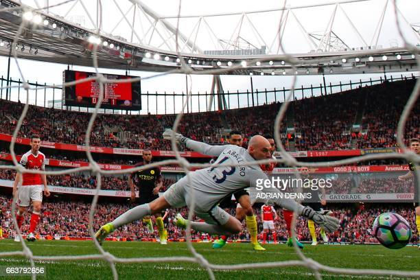 Arsenal's English midfielder Theo Walcott watches his shot beat Manchester CIty's Argentinian goalkeeper Willy Caballero for Arsenal's first goal...