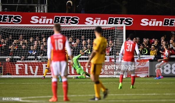 Arsenal's English midfielder Theo Walcott watches his shot beat Sutton United's English goalkeeper Ross Worner as he scores their second goal his...