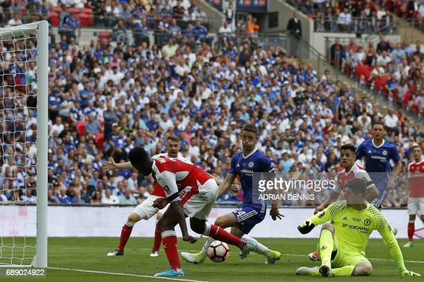 Arsenal's English striker Danny Welbeck beats Chelsea's Belgian goalkeeper Thibaut Courtois but cannot direct the ball at goal during the English FA...