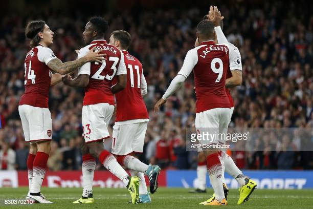 Arsenal's English striker Danny Welbeck celebrates with teammates after scoring their second goal during the English Premier League football match...