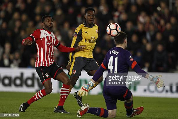 Arsenal's English striker Danny Welbeck chips the ball over Southampton's English goalkeeper Harry Lewis to score his team's first goal during the...