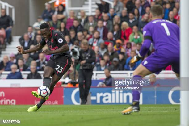 Arsenal's English striker Danny Welbeck has an unsuccessful shot as Stoke City's English goalkeeper Jack Butland prepares to save during the English...