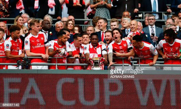 Arsenal's English striker Danny Welbeck holds the FA Cup trophy as Arsenal players celebrate their victory over Chelsea in the English FA Cup final...