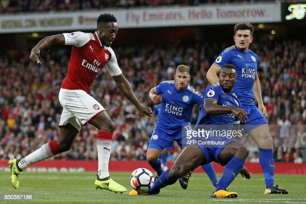 Arsenal's English striker Danny Welbeck L0 runs past Leicester City's Englishborn Jamaican defender Wes Morgan during the English Premier League...