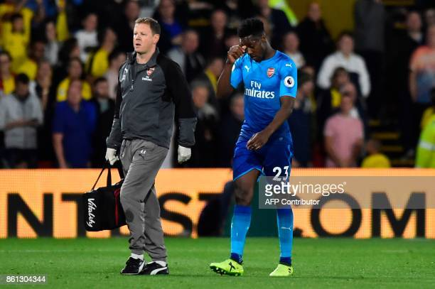Arsenal's English striker Danny Welbeck leaves the pitch substituted after recieving treatment for an injury during the English Premier League...