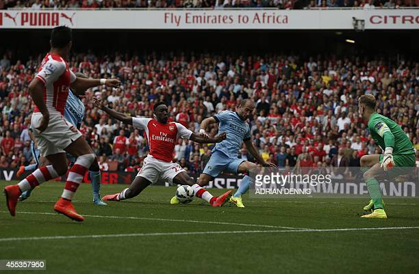 Arsenal's English striker Danny Welbeck takes a shot at goal as Manchester City's Argentinian defender Pablo Zabaleta attempts to block him during...