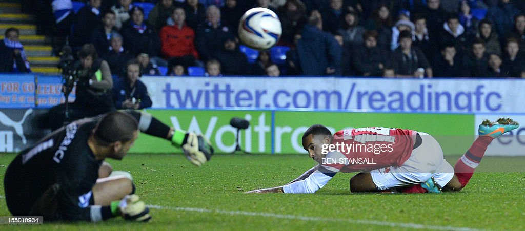 """Arsenal's English striker Theo Walcott (R) looks on as Reading's Australian goalkeeper Adam Federici (L) saves his shot during extra time in the English League Cup Fourth Round football match between Reading and Arsenal at The Madejski Stadium, in Reading, England on October 30, 2012. USE. No use with unauthorized audio, video, data, fixture lists, club/league logos or """"live"""" services. Online in-match use limited to 45 images, no video emulation. No use in betting, games or single club/league/player publications"""