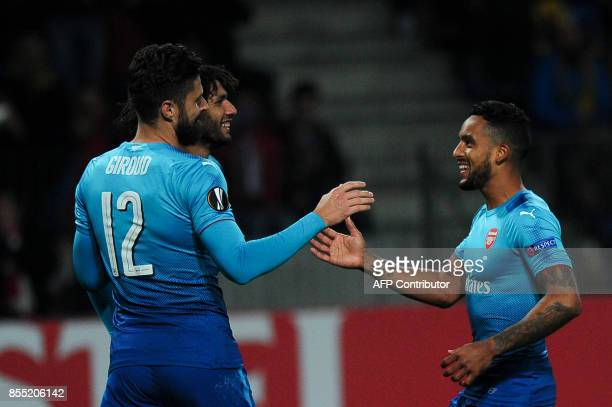 Arsenal's forward from France Olivier Giroud celebrates with teammates after scoring a goal from the penalty spot during the UEFA Europa League Group...