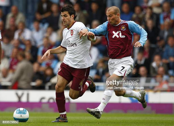 Arsenal's Francesc Fabregas and West Ham United's Fredrik Ljungberg battle for the ball