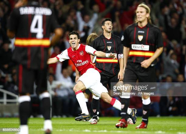 Arsenal's Francesc Fabregas celebrates an own goal by Sevilla's Julien Escude