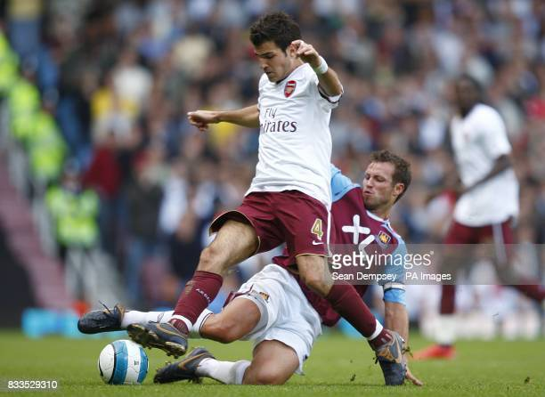 Arsenal's Francesc Fabregas is challenged by West Ham United's Lucas Neill as they battle for the ball