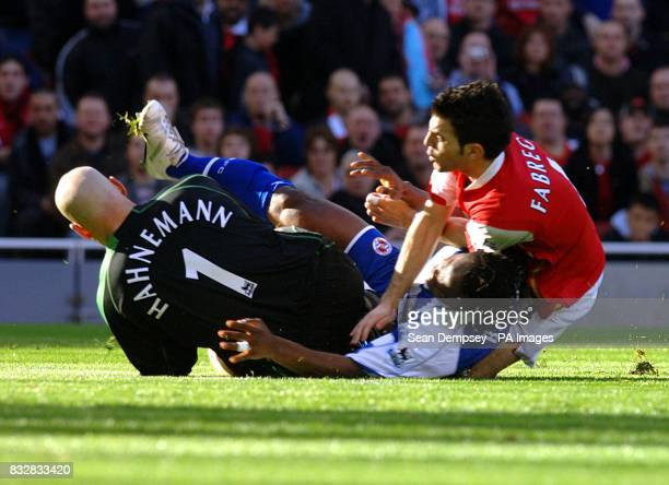 Arsenal's Francesc Fabregas is denied by Reading goalkeeper Marcus Hahnemann and Andre Bikey