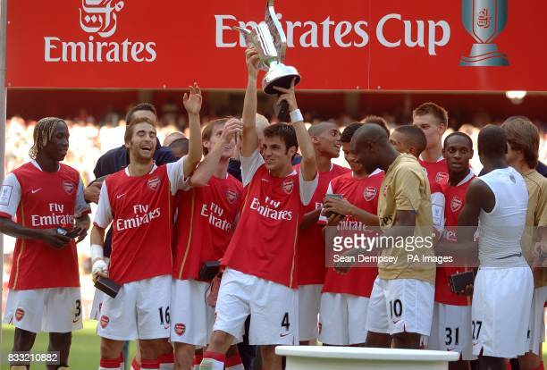 Arsenal's Francesc Fabregas lifts the trophy as his team celebrates winning the Emirates Cup