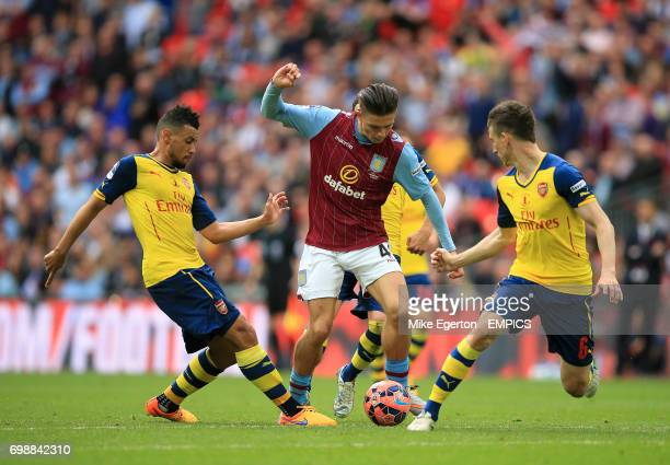 Arsenal's Francis Coquelin and Arsenal's Laurent Koscielny battle for the ball with Aston Villa's Jack Grealish