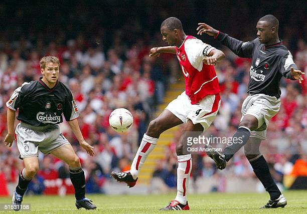 Arsenal's French captain Patrick Vieira is challenged by Emile Heskey and Michael Owen of Liverpool during the FA Community Shield match at the...