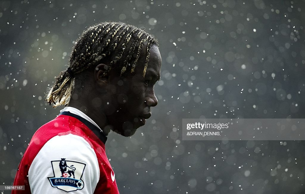 """Arsenal's French defender Bacary Sagna looks on in the falling snow during the game between Chelsea and Arsenal during the English Premier League football match at Stamford Bridge in London on January 20, 2013. Chelsea won the game 2-1. USE. No use with unauthorized audio, video, data, fixture lists, club/league logos or """"live"""" services. Online in-match use limited to 45 images, no video emulation. No use in betting, games or single club/league/player publications."""
