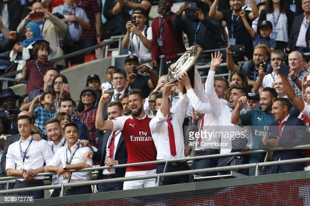 Arsenal's French defender Laurent Koscielny and Arsenal's German defender Per Mertesacker hold up the trophy as they celebrate after their victory in...