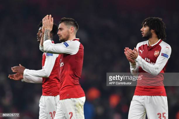 Arsenal's French defender Mathieu Debuchy and Arsenal's Egyptian midfielder Mohamed Elneny gesture after the UEFA Europa League Group H football...