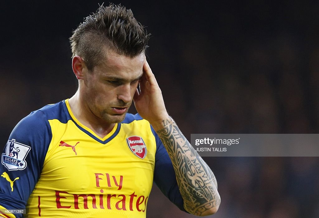 Arsenal's French defender Mathieu Debuchy touches the side of his head after a foul during the English Premier League football match between West Ham...