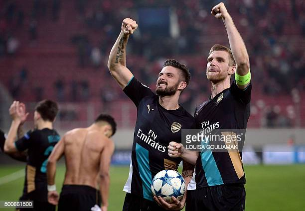 Arsenal's French forward Olivier Giroud and Arsenal's German defender Per Mertesacker celebrate after the UEFA Champions League Group F football...